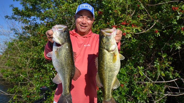 Bob Izumi holds up two fish he caught.