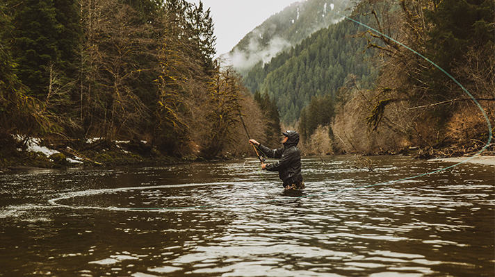Curtis Ciszek casting away from the middle of a river.