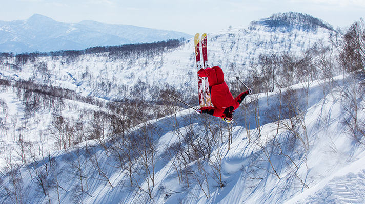 Alex Ferreria in midair doing a backflip on a mountain slope.