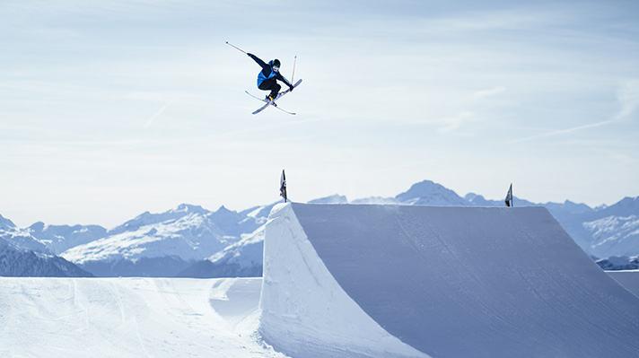 Sarah Hoefflin flying off a freestyle ski jump.