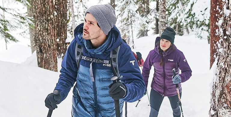 A man and woman snowshoeing with Columbia accessories like hats, gloves, and packs.
