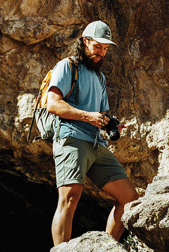 A man standing on a rocky trail with a camera.