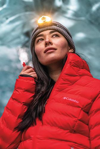 A woman outside in a warm coat wearing a headlamp.