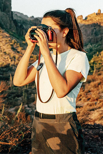 A woman with a camera in a desert landscape.