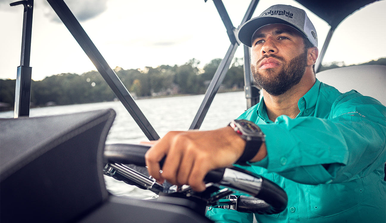 Close-up of Bubba Wallace piloting a boat while wearing Columbia PFG.