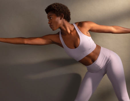 A woman holding a yoga pose represents prAna's collection of yoga styles for women.