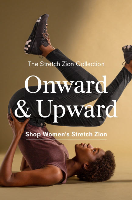 A woman wearing Stretch Zion pants strikes an upside-down pose.