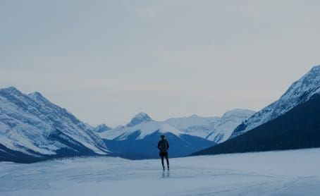 solitary figure stands among snow and ice with snow-capped mountains on the horizon