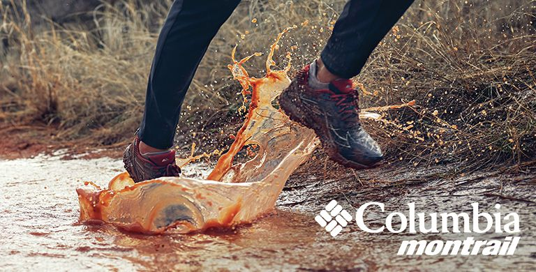 Close-up of a trail runner running through a mud puddle.