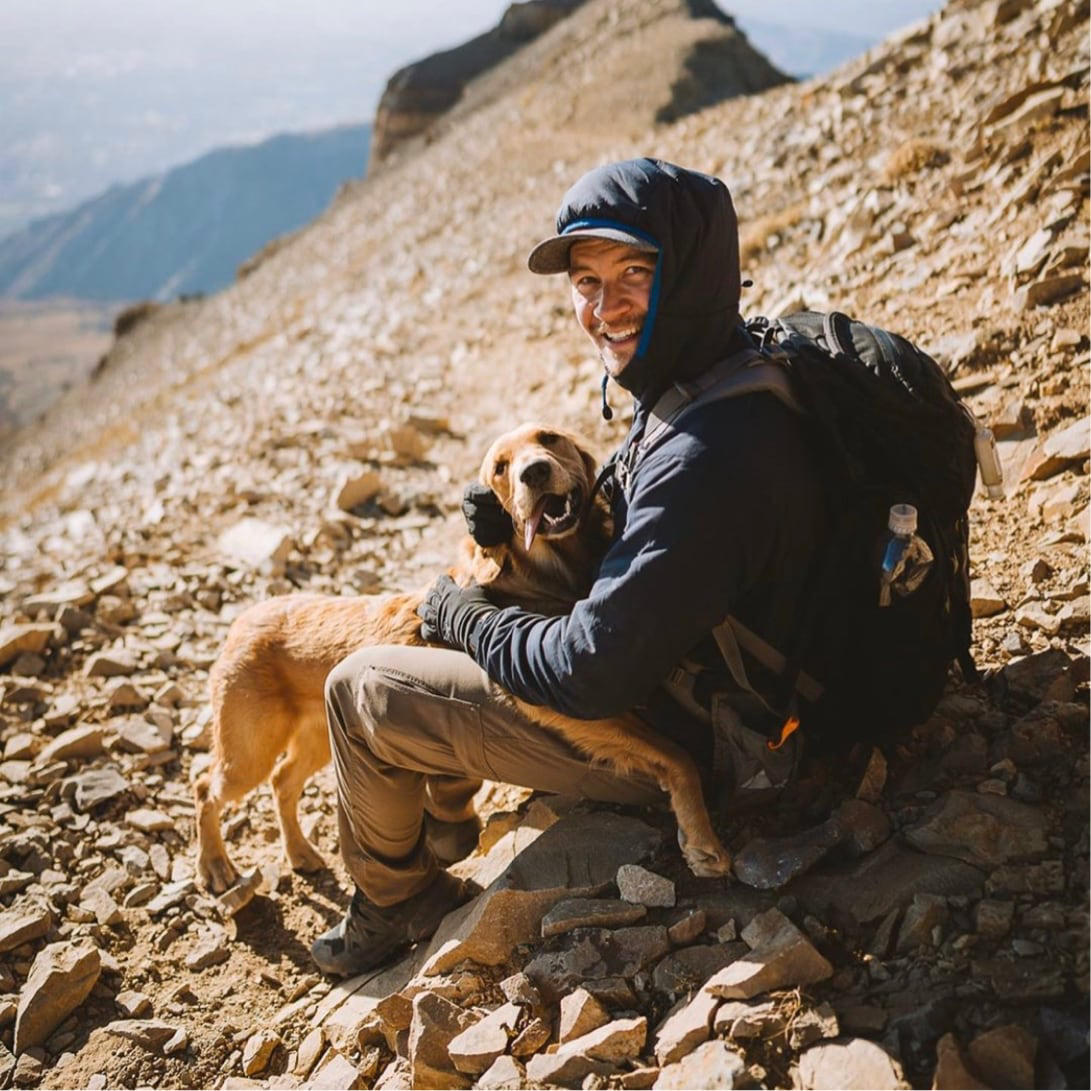A man wearing a backpack and Stretch Zion pants sits with his dog while on a hike in the mountains.