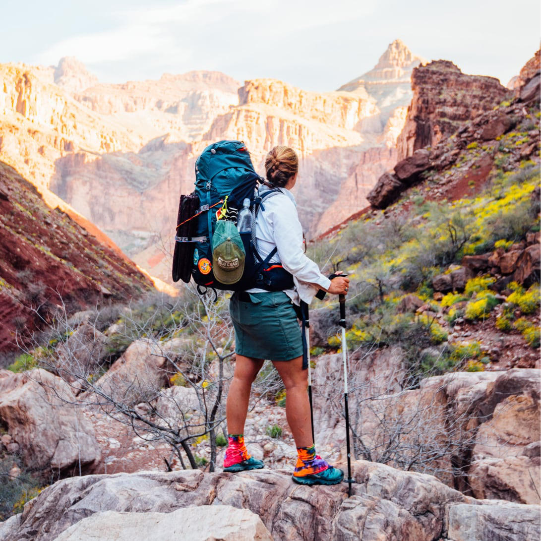 A woman on a backpacking trip wearing a stretch zion skirt stands in front of a large canyon.