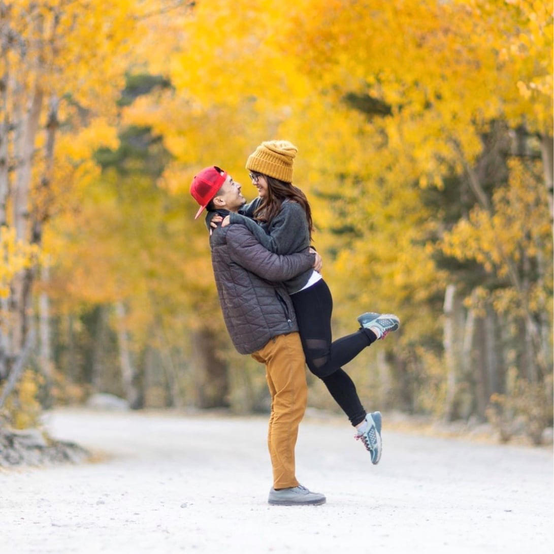A man wearing stretch zion pants embraces a woman in the middle of an unpaved road.