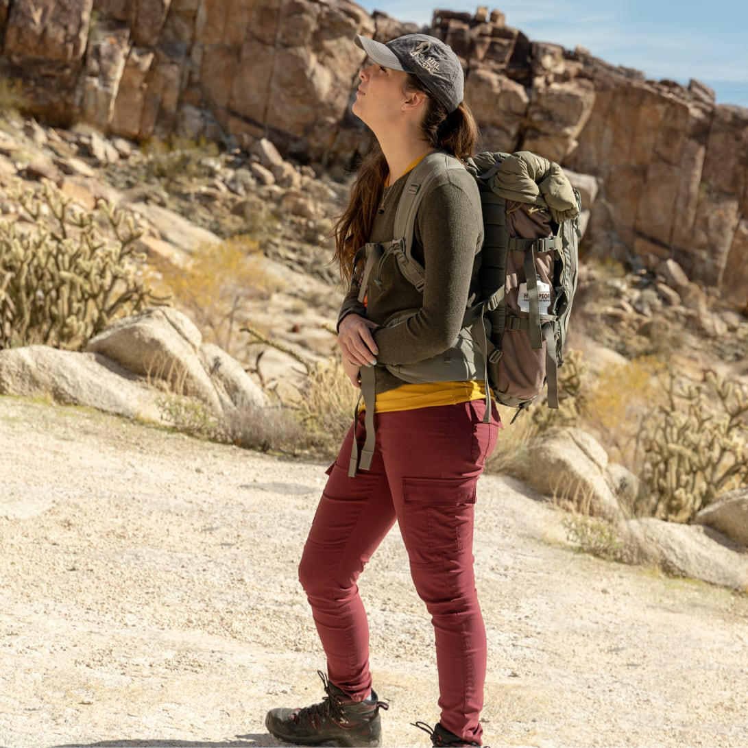 A woman on a backpacking trip wearing stretch zion pants stands still looking at the path ahead of her.