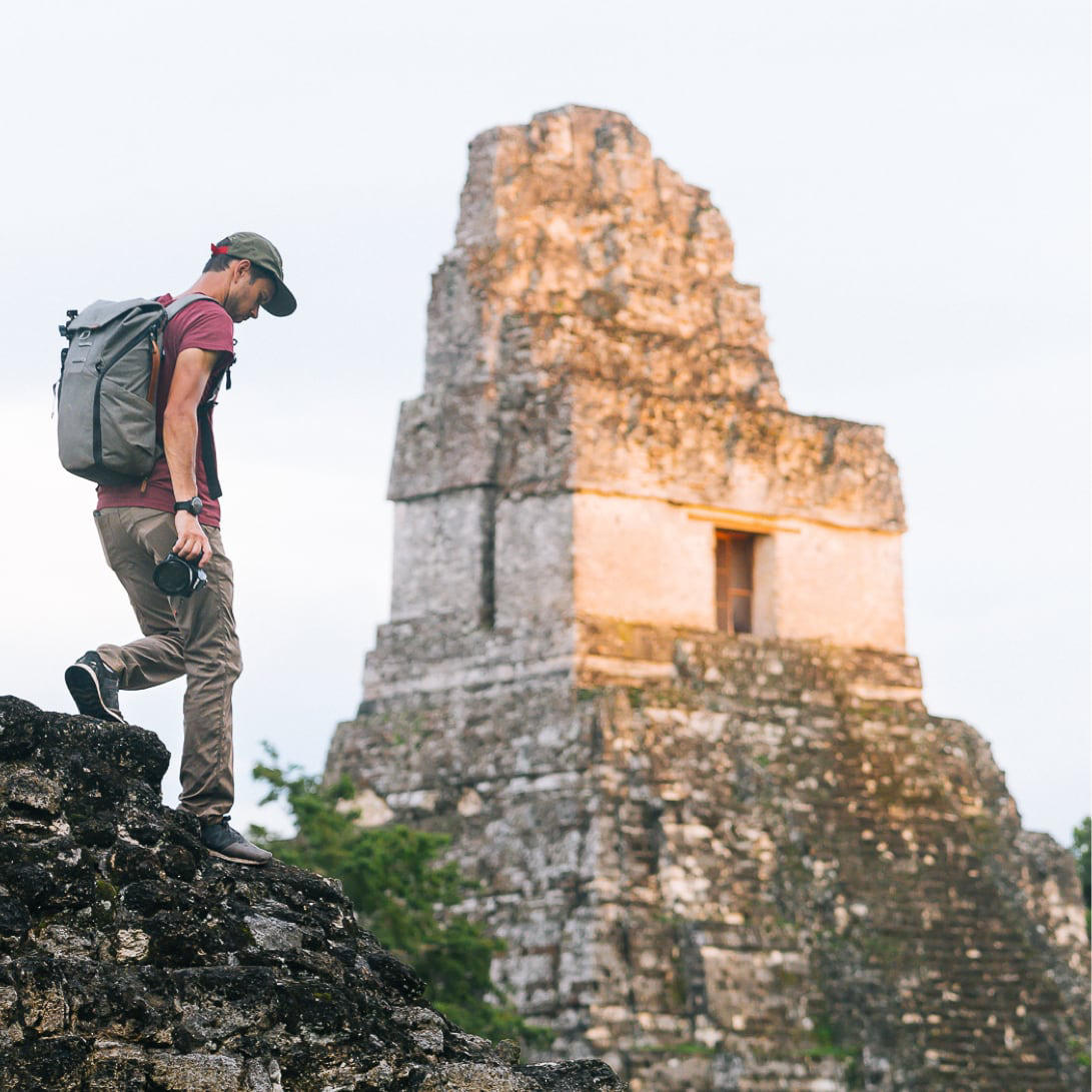 A man wearing Stretch Zion pants hikes along a ledge that sits in front of an ancient ruin.