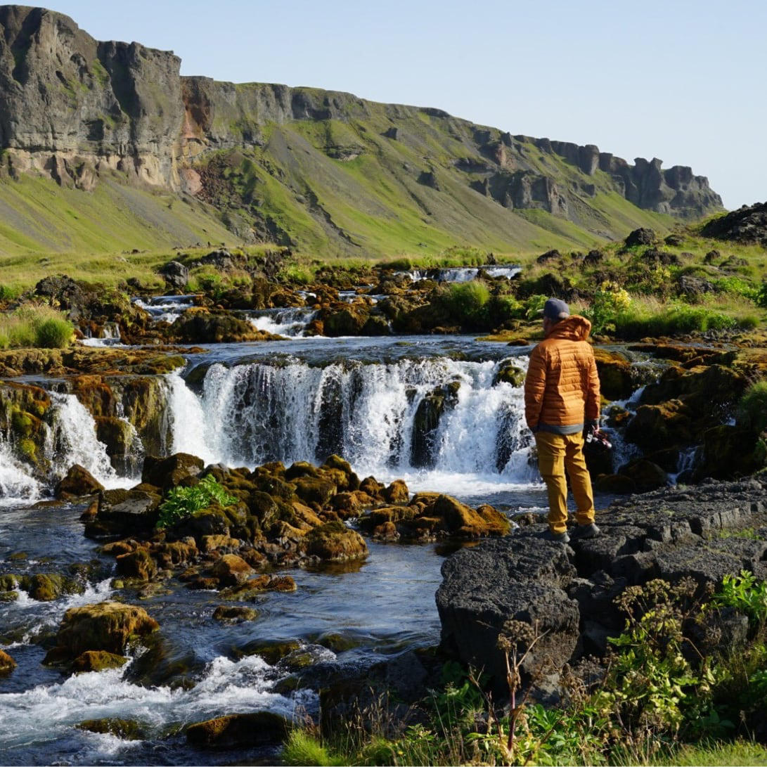 A man wearing yellow Stretch Zion pants stands on the edge of a river.