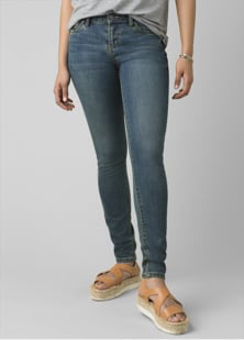 A woman wearing dark wash, skinny-leg jeans and tan sandals.