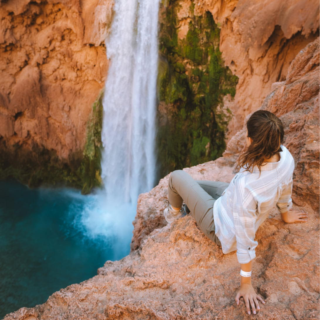 A woman sits above a waterfall wearing stretch zion pants.