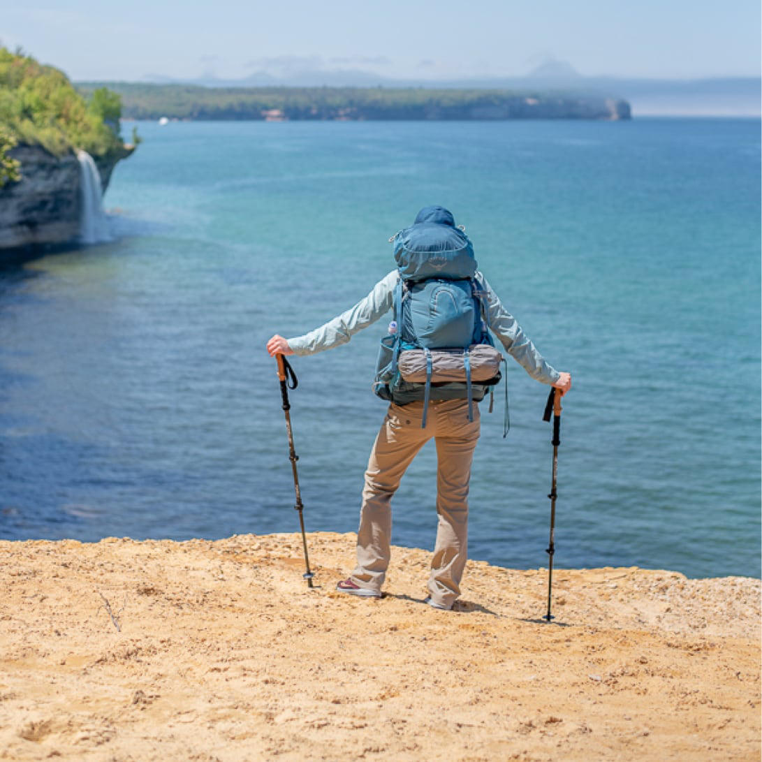 A woman on a backpacking trip wearing stretch zion pants stands in front of an ocean view.