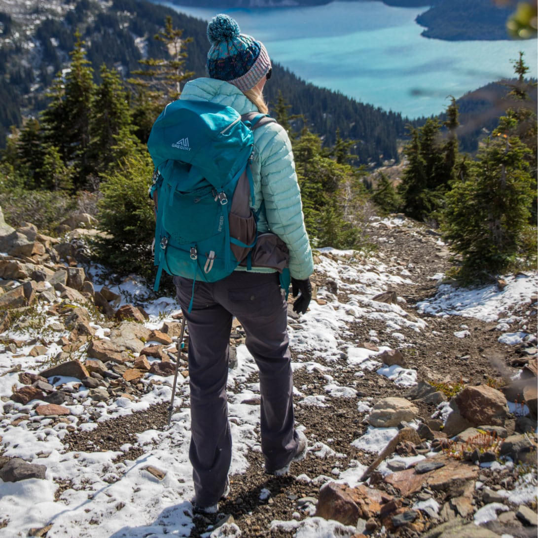 A woman on a backpacking trip wearing stretch zion pants stands above a lake mountain lake.