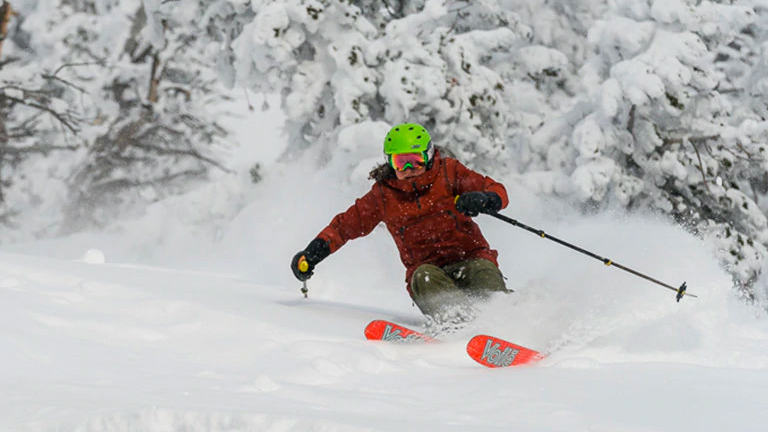 Whiteout, fresh powder conditions as a skier comes down the mountain in the backcountry.