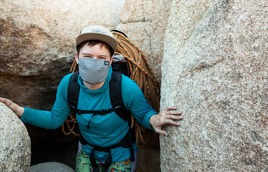 Mari between two boulders, smiling at the camera under her mask.