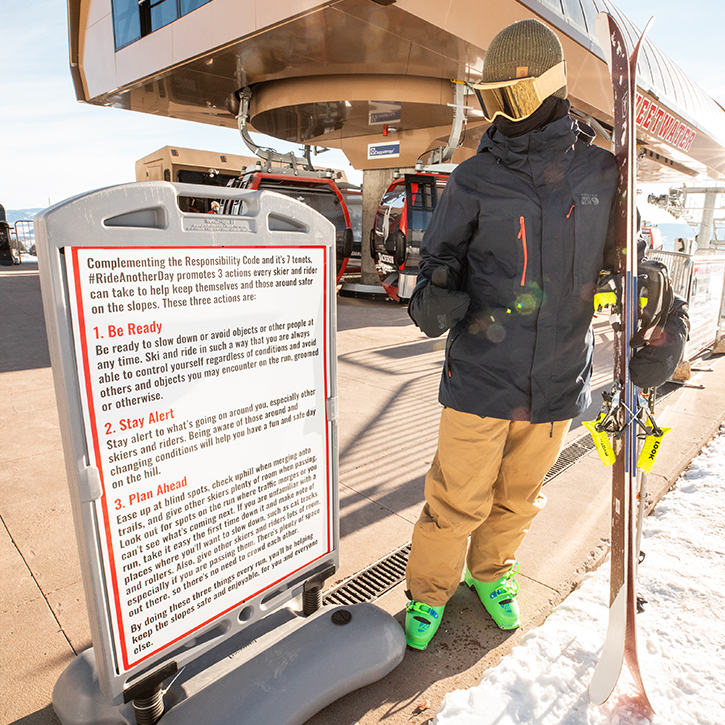 Reading the guidelines posted near the bottom of the chairlift at a ski resort