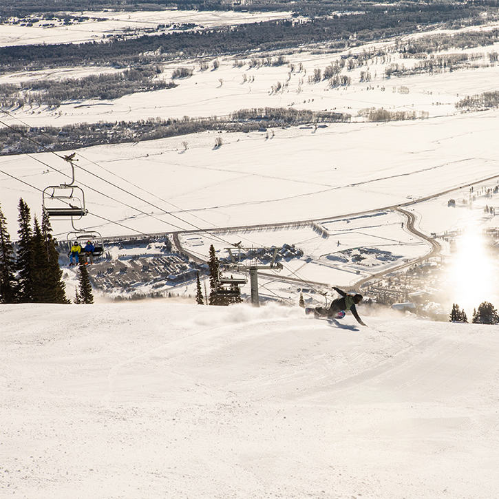 In a resort, a skier makes their way down the run, near the chairlift