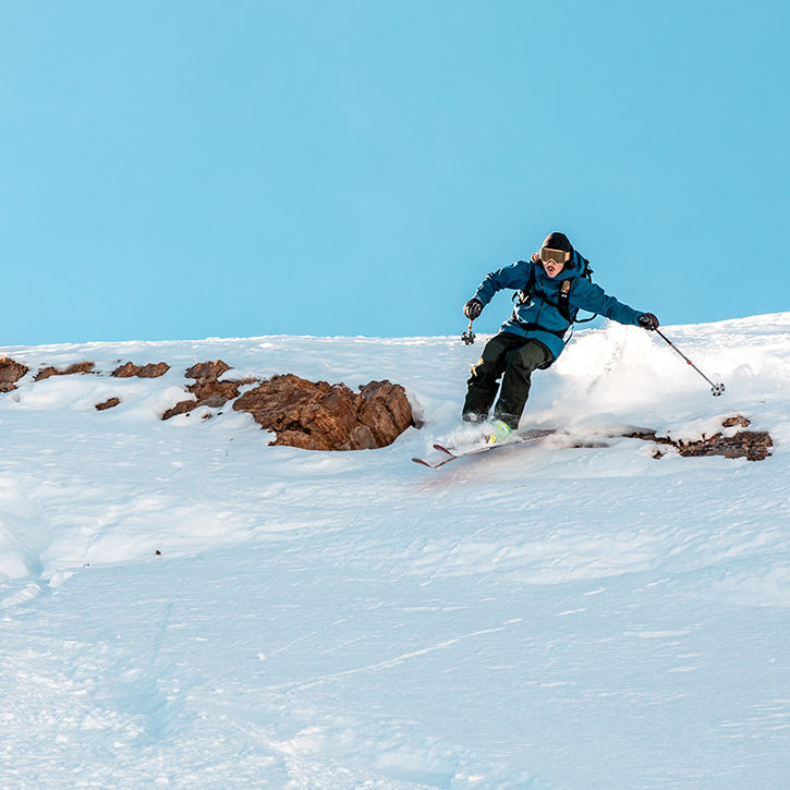A skier jumps over some rocks on a rough sidecountry run