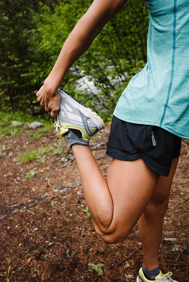 A woman wearing Columbia Montrail gear stretching before a run.