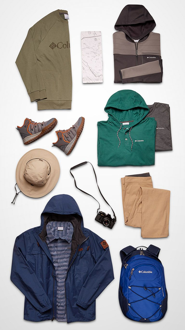 A top-down image of jackets, pants, hats, packs, shoes and a camera.