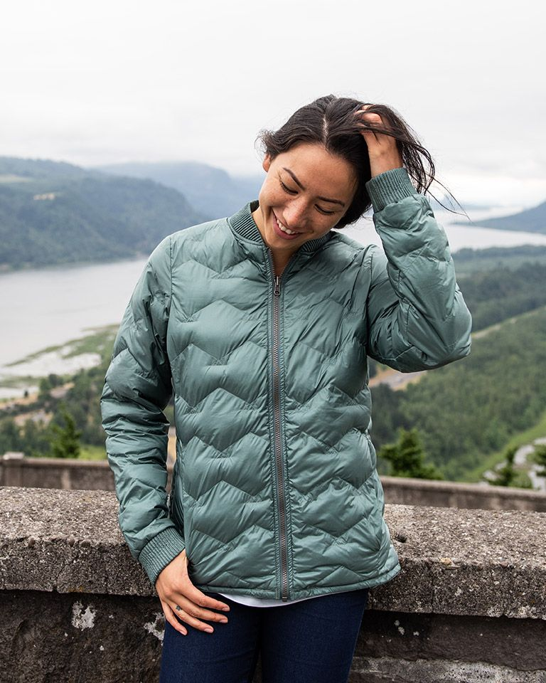 A woman in a jacket hiking.