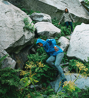 Two people scrambling down a rocky hillside.