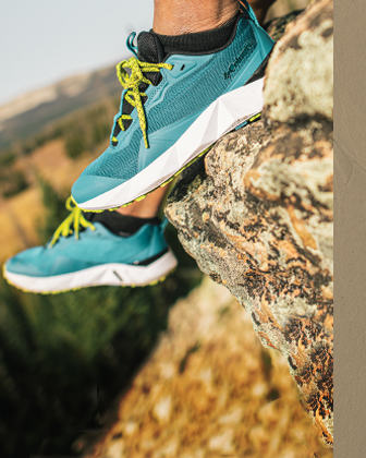 A close up of feet in Columbia footwear atop a rock