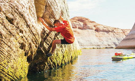 A man rock climbing above water in gear featuring Omni-Freeze Zero Ice.
