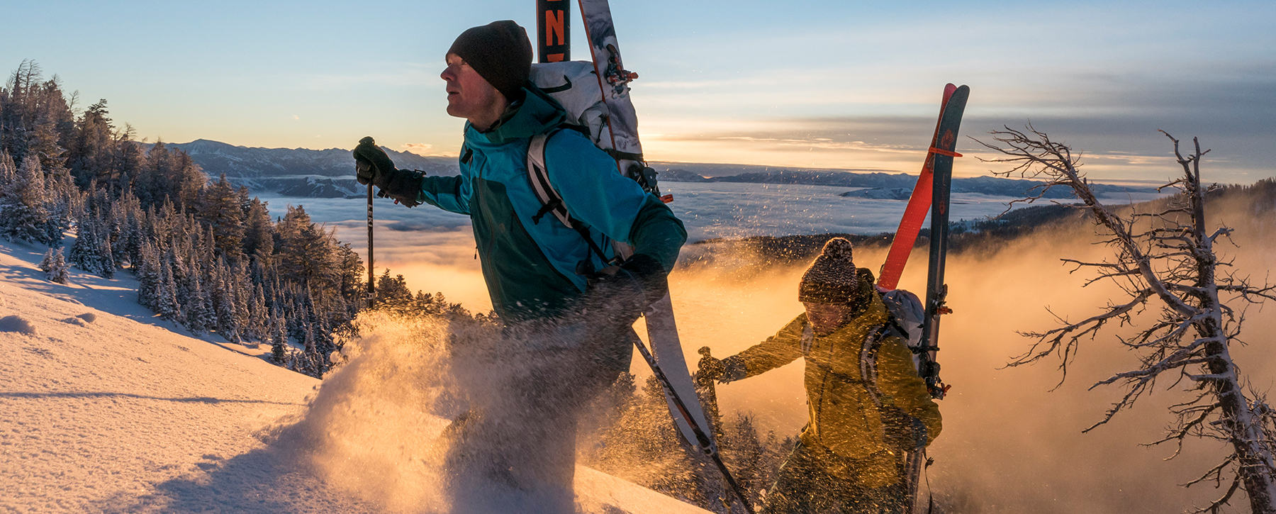Two skiers hiking their way up in the backcountry at sunrise.
