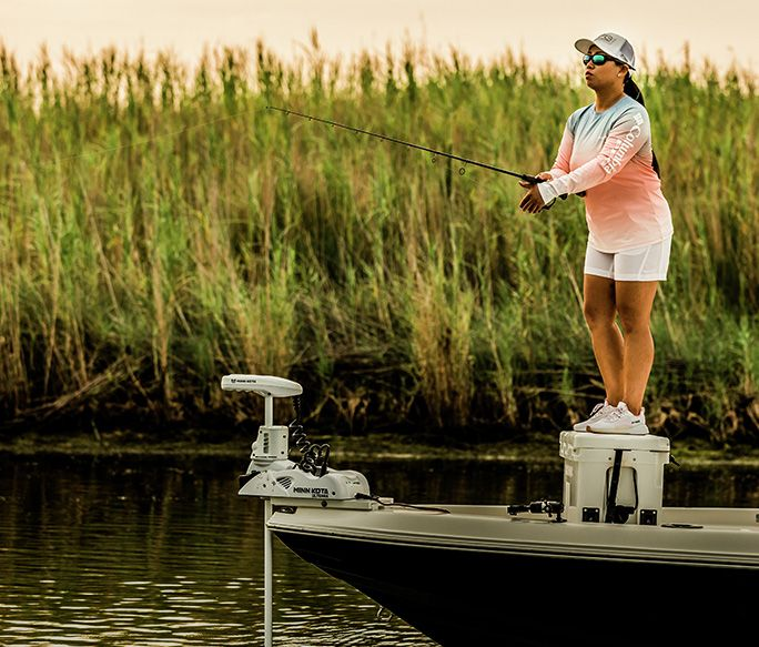 A woman wearing PFG fishing from a boat.