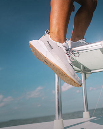 Zoomed in shot of feet in PFG shoes on a boat
