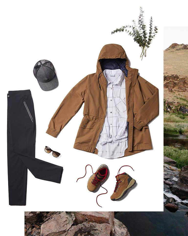 Lay-down image of womens rugged pants, jacket, boots, cap, sun glasses, and fern.