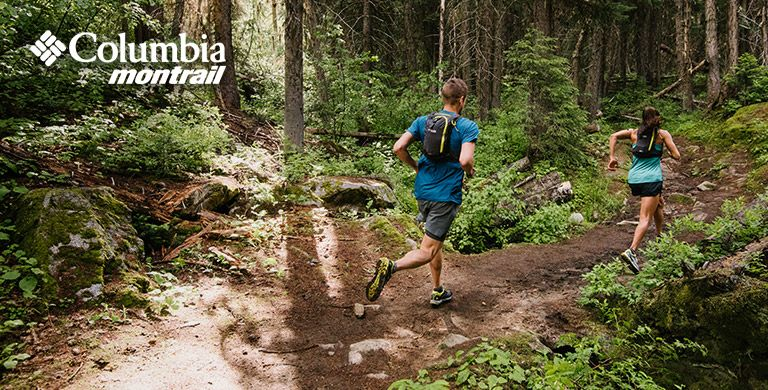 Two trail runners in a forest, Columbia Montrail logo.