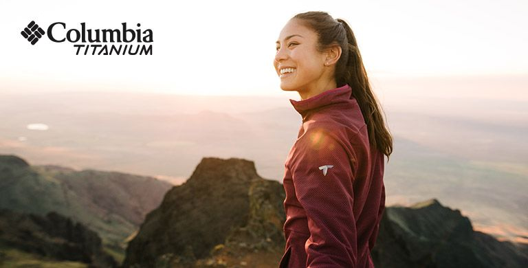 Two hikers in a high rocky terrain, Columbia Titanium logo.