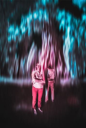 Infrared image of two campers at night in the foreground, blue and pink light lines in the background.