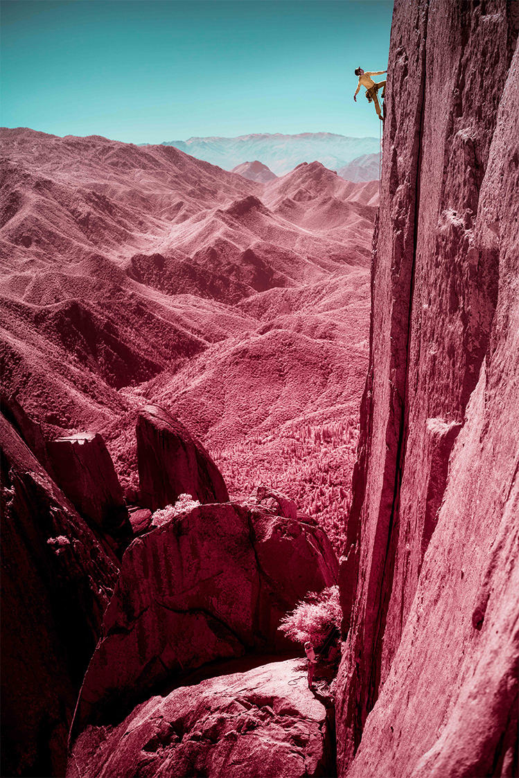 Infrared image of MHW athlete Miranda Oakley looking up for her next move, close to the top of a route.