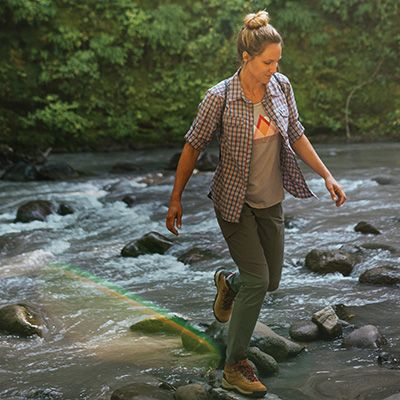 A woman in Columbia gear hiking across a stream.
