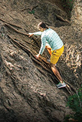 爬上一个陡峭的岩石倾斜的人。