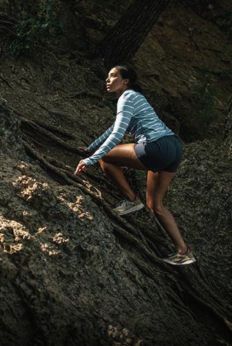爬上陡峭的岩石倾斜的妇女。
