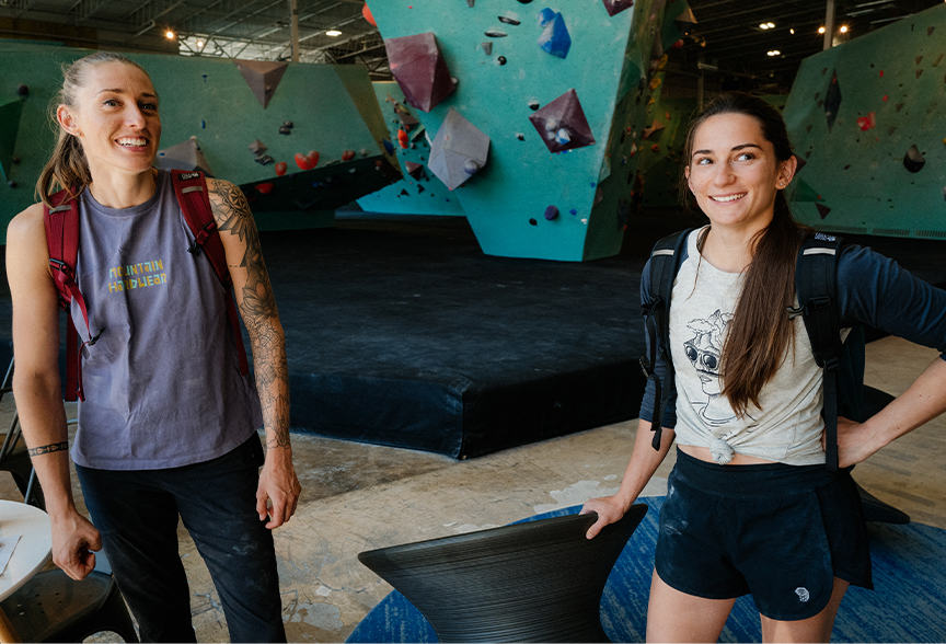 Alex Johnson and Kyra Condie smile for the camera inside the climbing gym, both with backpacks on, ready to go.