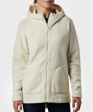 A woman wearing a cream-colored Sherpa fleece hoodie.