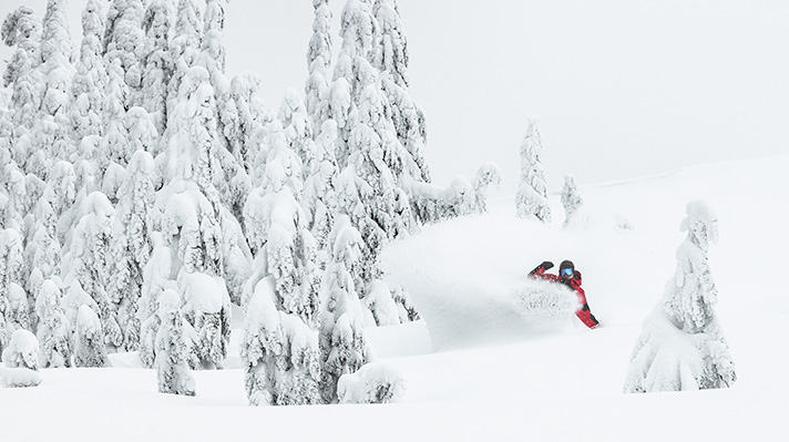 Curtis Ciszek snowboarding through deep powder.