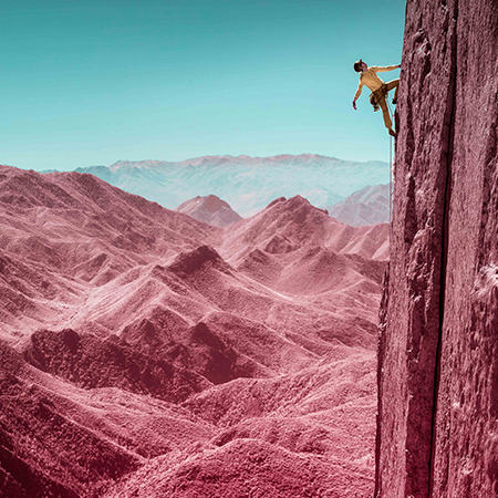 Infrared image of a climber looking up for her next move, close to the top of a route.