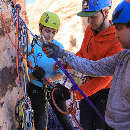 In a climbing clinic by The Mountain Guides, they show a participant all the ins and outs of clipping in and creating an anchor.